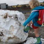 Wirbelwind tritt gegen eine Schneekugel. Dabei trägt sie nur Kleid, Jacke und Gummistiefel, aber keine lange Hose.