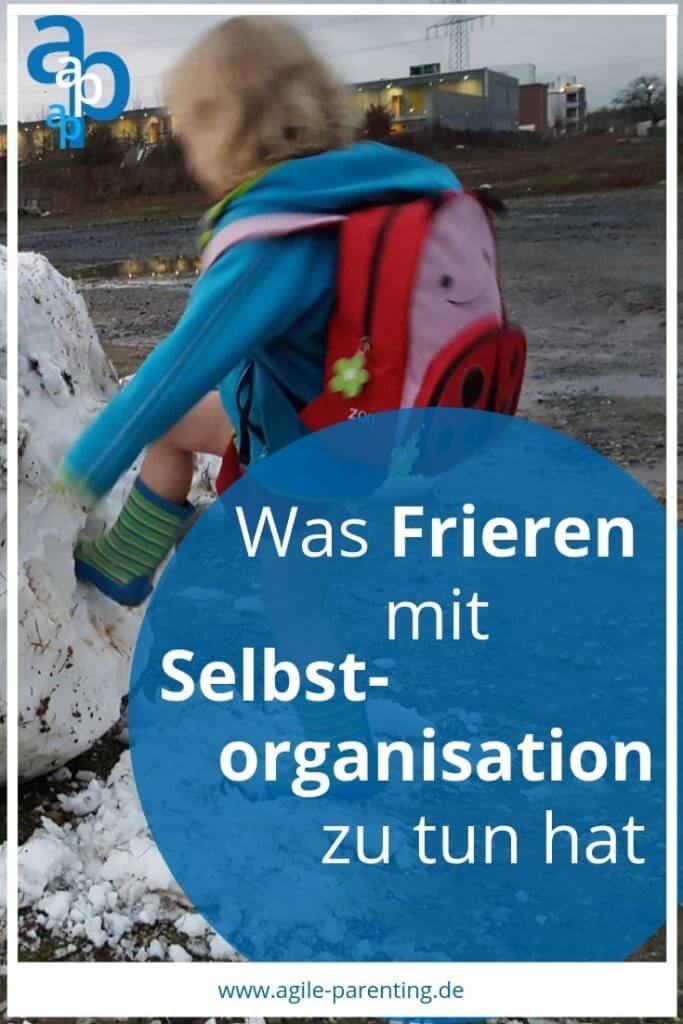 Ein Kind tritt auf einen Schneehaufen mit Gummistiefeln, Kleid und Jacke, aber ohne Hose