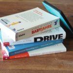 """Ein Stapel Bücher, u.a. sind zu sehen: """"Drive"""" von Dan Pink und ein Kindle E-Reader"""