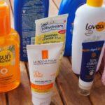 Viele verschiedene Sonnenschutzmittel und ein Sonnenhut