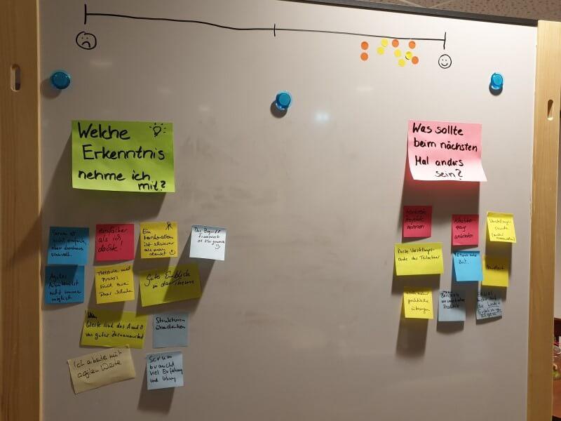 """Feedback-Wand mit Skala und Klebezetteln zu den Fragen """"Was nehme ich mit?"""" und """"Was sollte beim nächsten Mal anders sein?"""""""