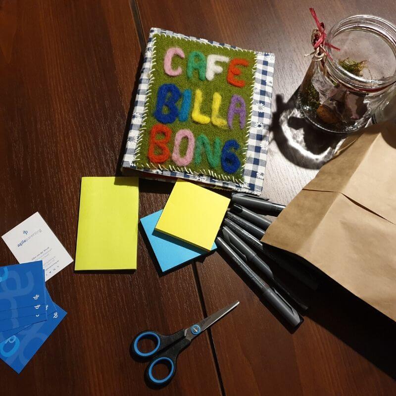 Menükarte des Café Billabong und Workshop-Materialien wie Schere, Stifte, Post-Its auf einem Tisch