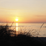 Kind rennt am Strand bei Sonnenuntergang