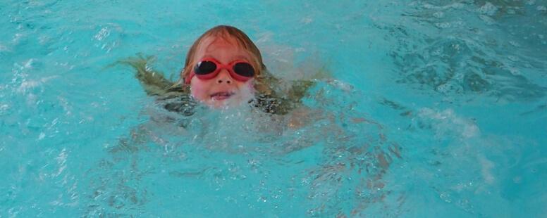 Kind schwimmt im Wasser
