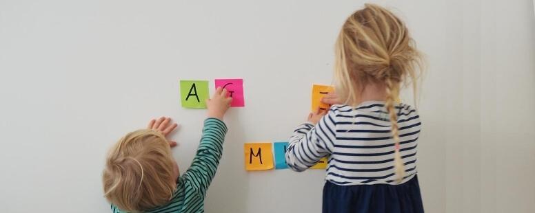 Zwei Kinder kleben Post-Its an eine Wand